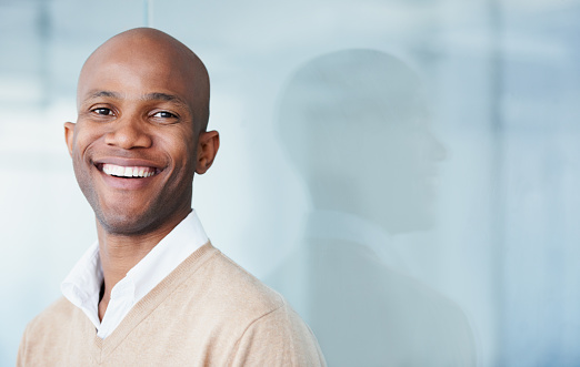 Young black man smiling with blue background